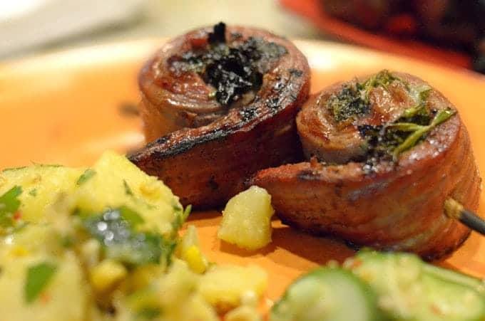 Serving of steak pinwheels on a skewer and plate.