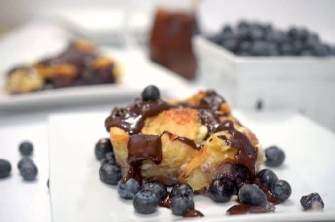 A close up of blueberry bread pudding on a plate.