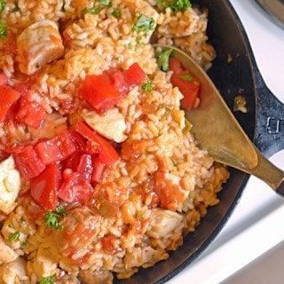 A skillet with a wooden spoon with Jambalaya and Sausage