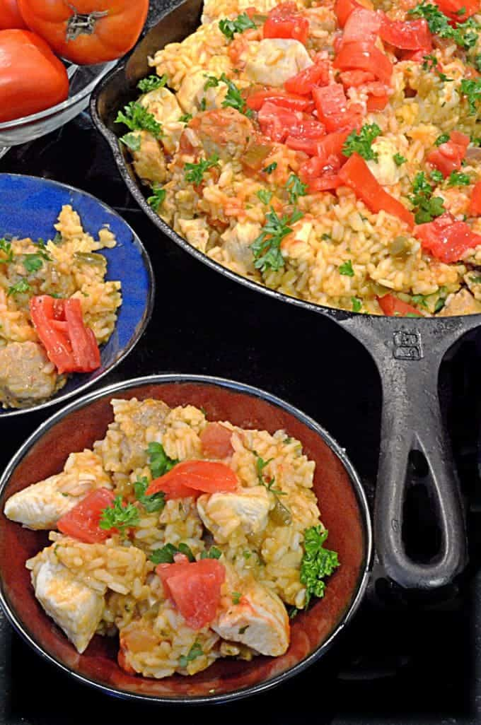 A skillet and two dishes filled with Jambalaya and Chicken
