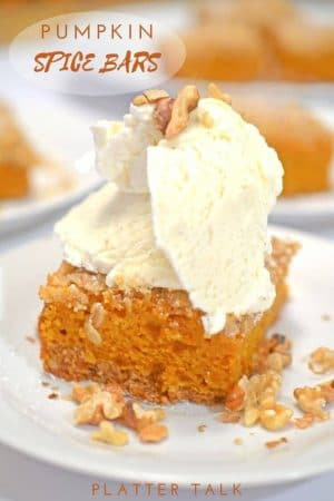 Serving of pumpkin spice dessert bar topped with ice cream.