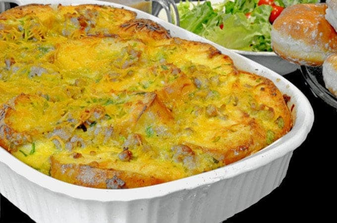 Pan of baked breakfast sausage casserole with bowl of salad in background.