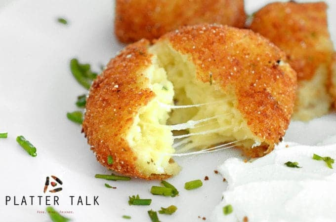 Mashed potato croquette split in half with stringy cheese within.