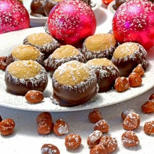 Plate of buckey Christmas treats with ornaments and hazelnuts.