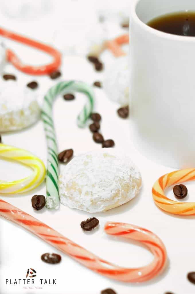 White mug of coffee surrounded by snowball cookies and candy canes.