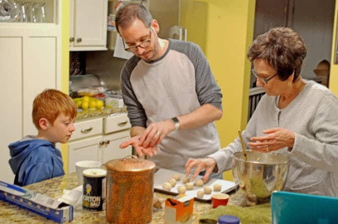 Young boy with father and grandmother, making Christmas cookies.