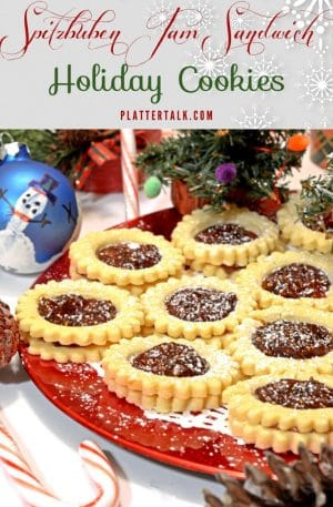 Spitzbuben Jam Sandwich Holiday Cookies on a festive red platter with Christmas decorations.