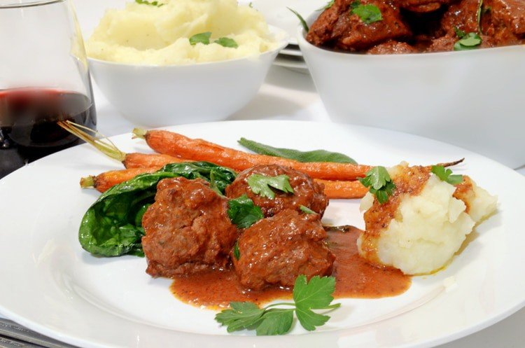 Serivng plate of braised meatballs, carrots, and mashed potatoes.