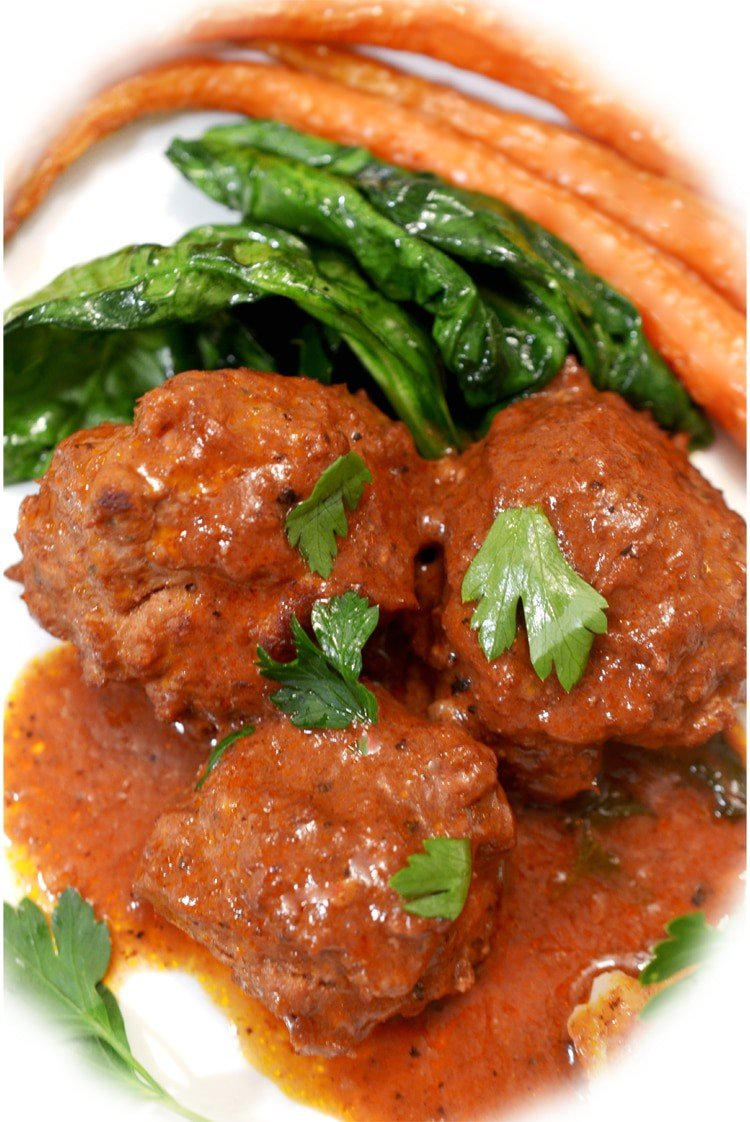 plateof meatballs surrounded by carrots.