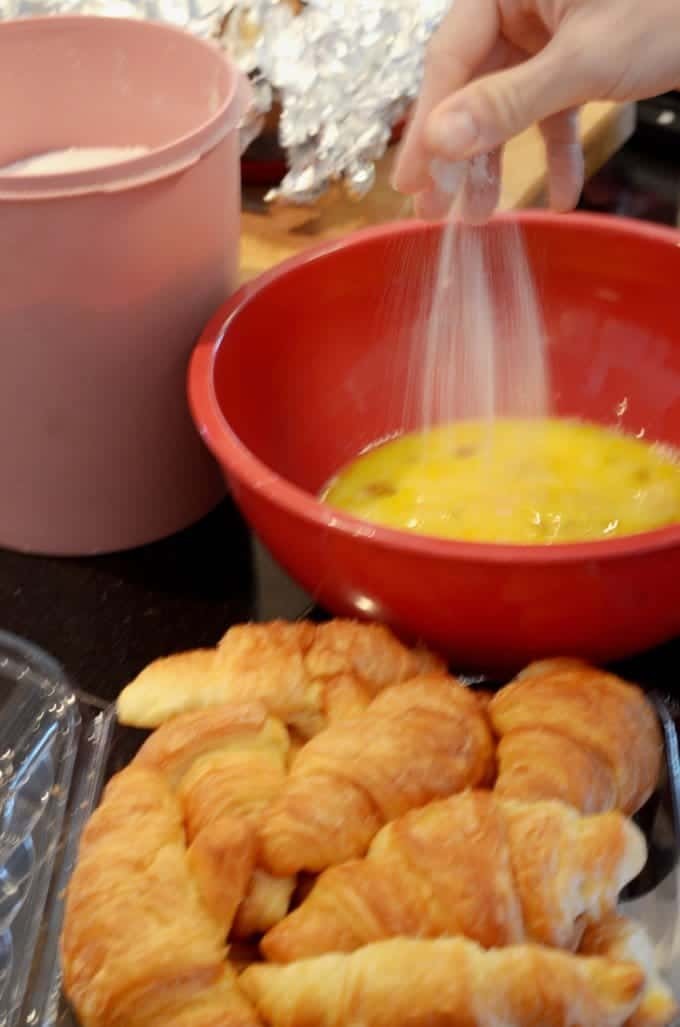Plate of croissants with mixing bowl and beaten eggs.