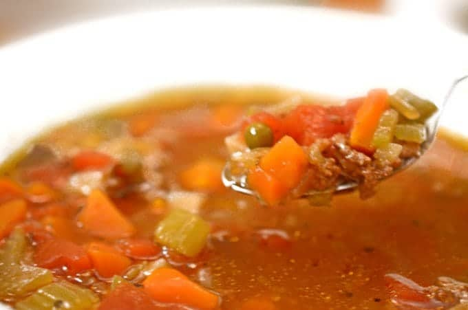Spoonful of soup with ground beef and vegetables.