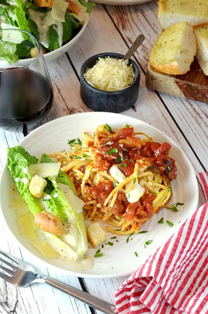 A plate of sauced spaghetti and romaine salad sitting on tble