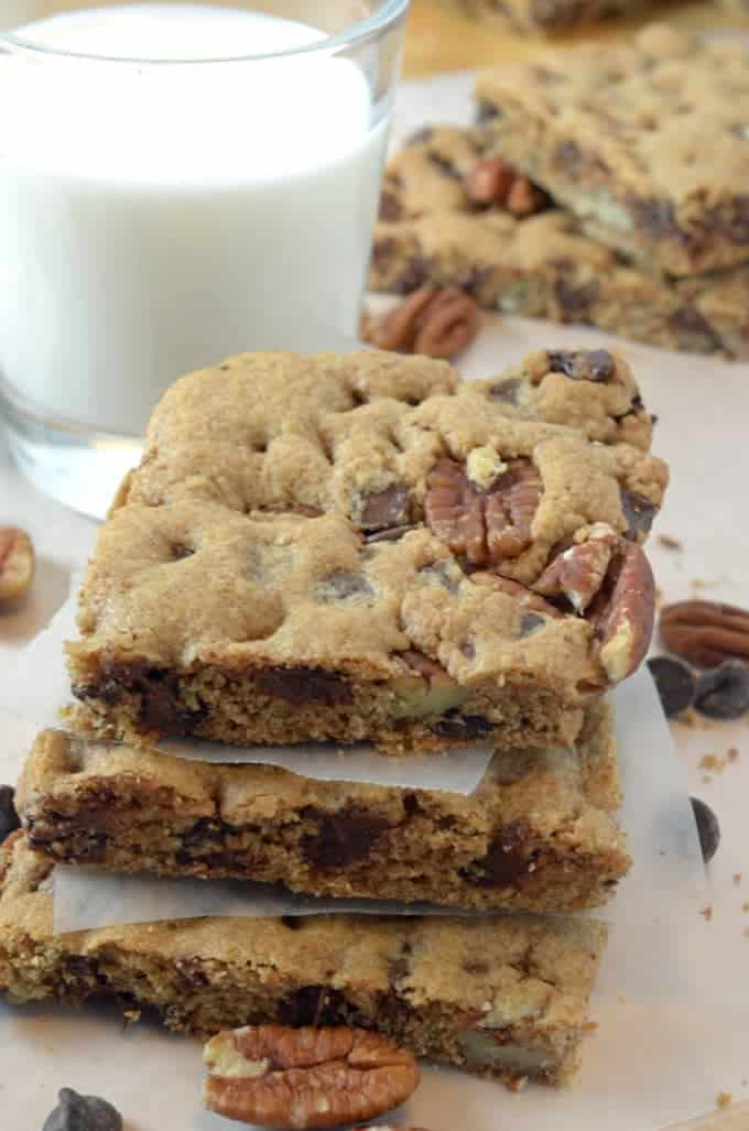 A stack of cookie bars with a glass of milk