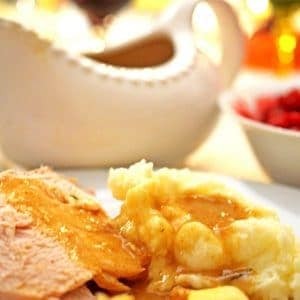 Mashed potatoes with turkey gravy and roasted turkey on a plate.