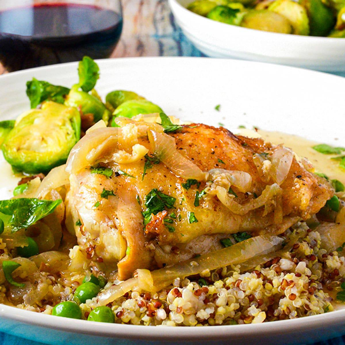 Seared chicken thigh on a serving plate with quinoa and Brussels sprouts.