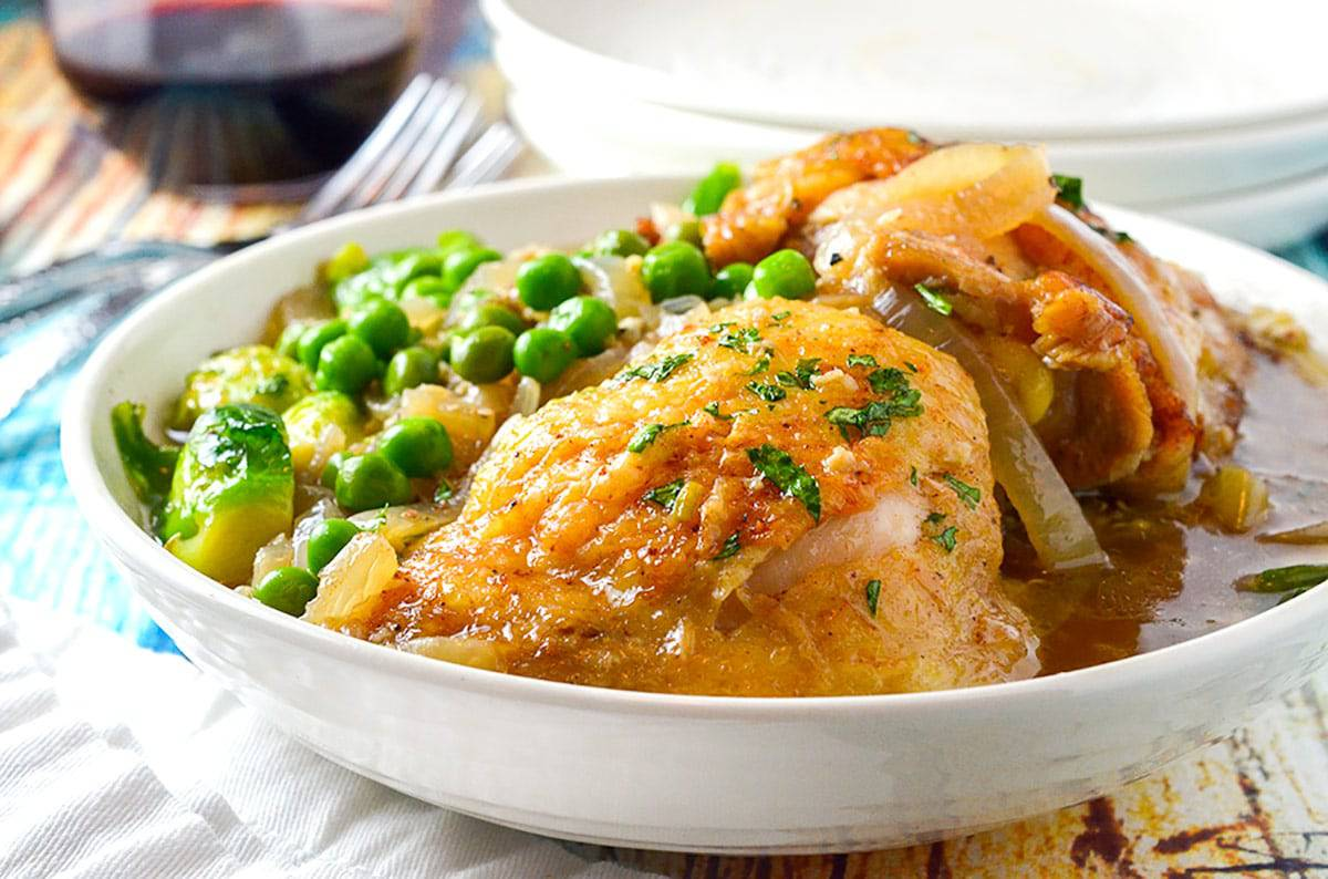 Bowl of seared chicken thigh and peas.