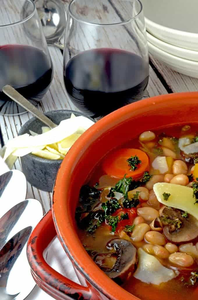 Bowl of winter soup with fresh herbs and wine.