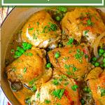 Skillet of chicken thighs with parsley garnish.