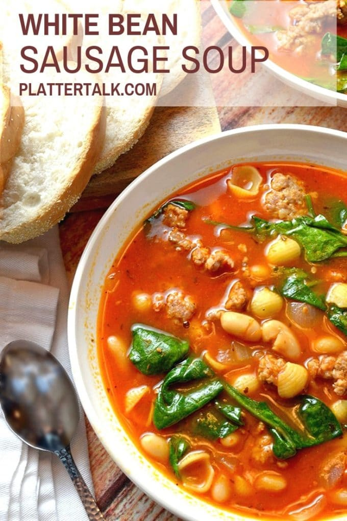 Bowl of white bean soup with sausage and spinach and homemade bread.