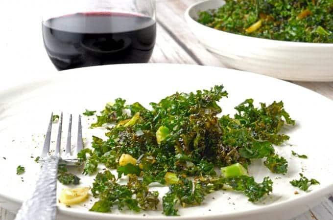 plate of crsipy kale salad with glass of red wine.