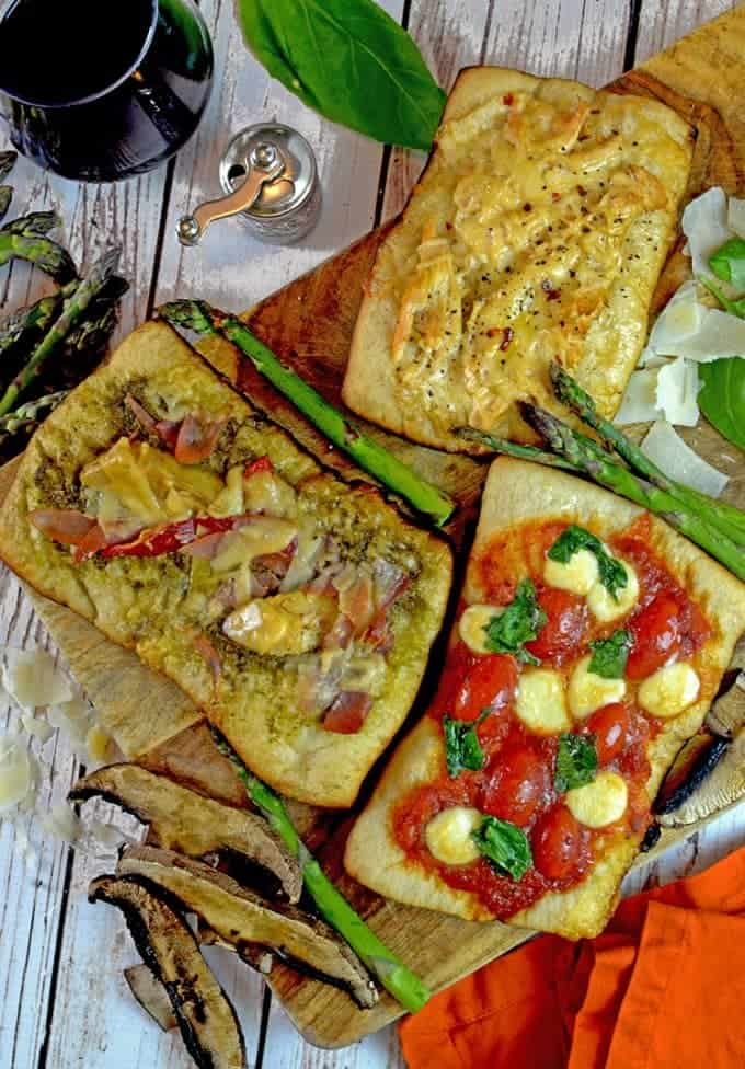Varieties of grilled pizza on cutting board