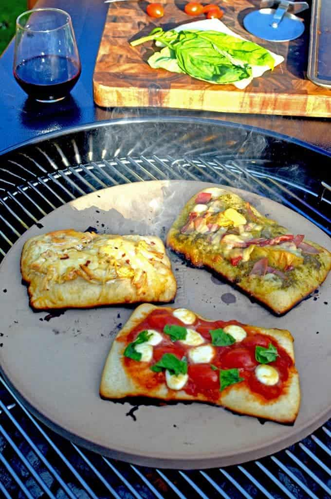 A pizza stone on bbq grill cooking 3 types of pizza