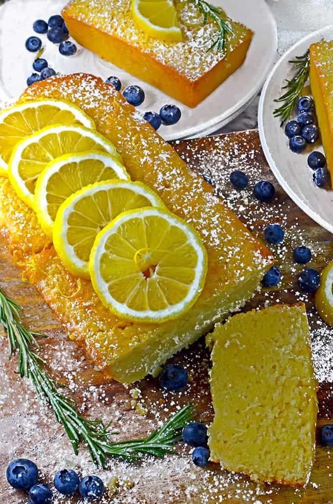 Garnish the lemon loaf cake recipe with fresh lemons, blueberries, and springs of rosemary.