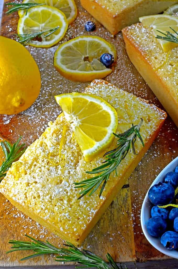 Lemon loaf cake with slices of oragne and sprigs of rosemary on a cutting board.