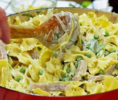 Creamy Pasta with Ham and Peas being stirred