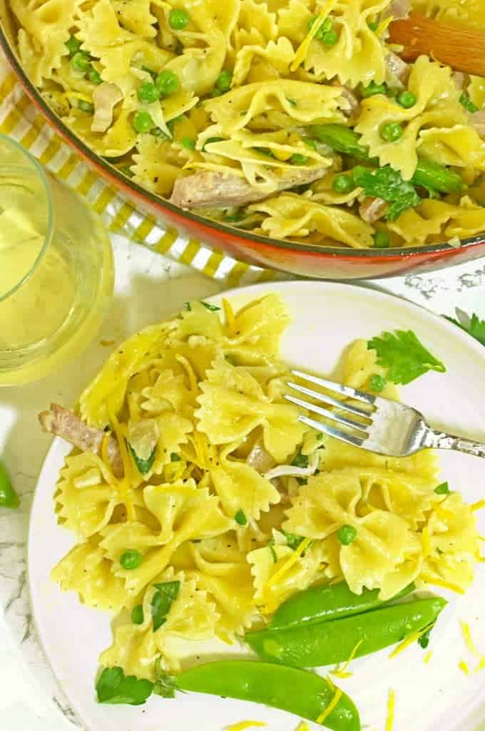 A serving of creamy pasta with ham and peas