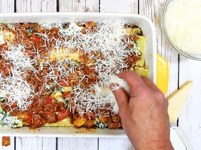 Spreading mozzarella cheese on the best easy lasagna recipe.