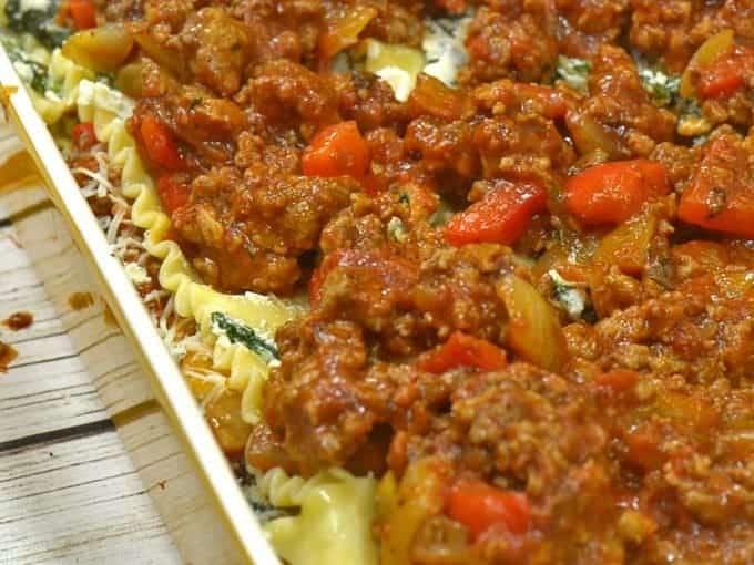 spreading marinara sauce on the best easy lasagna recipe.