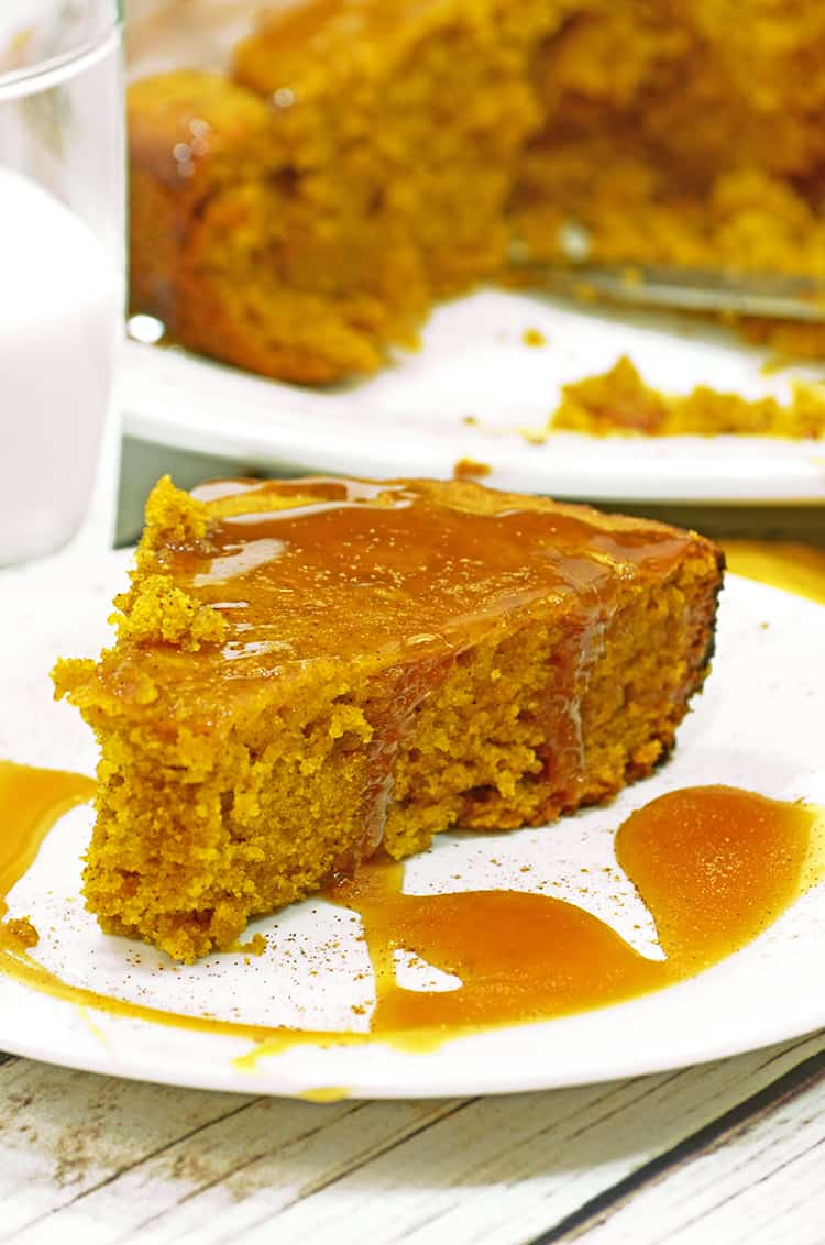 Slice of pumpkin cake with caramel sauce and a glass of milk.