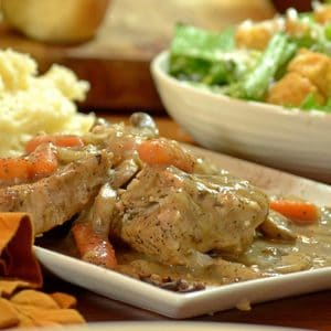 A plate meat, gravy, mashed potato with salad and croutons background