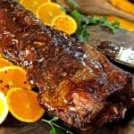 Rack of ribs with orange slices and a kitchen brush.