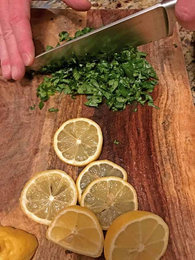 Chopping parsley and lemons on a cutting board.