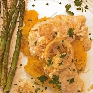 Chicken breast atop shredded squash, asparagus on side with lemon on top
