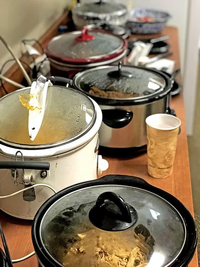 Crockpots lined up for a pot luck dinner.