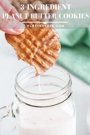 Dunking a peanut butter cookie into a glass of milk.
