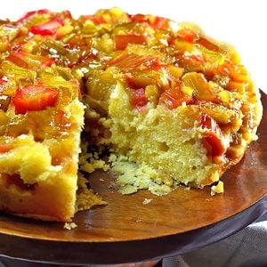 Rhubarb cake on a serving dish with slice cut out.