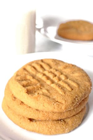Stack of easy peanut butter cookies with glass of milk.