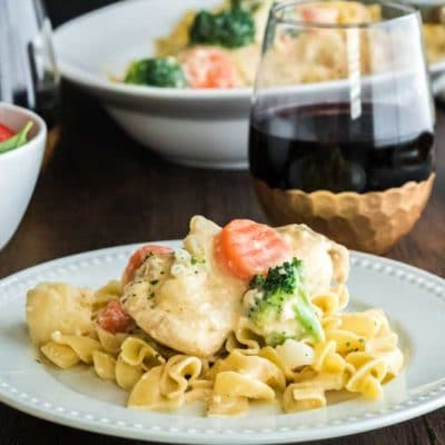 Plate of slow cooker chicken breast with eggnoodles and vegetasbles and glass of red wine.