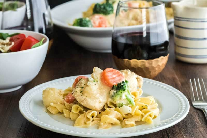 Plate of slow cooker chicken breast with egg noodles and vegetasbles and glass of red wine.
