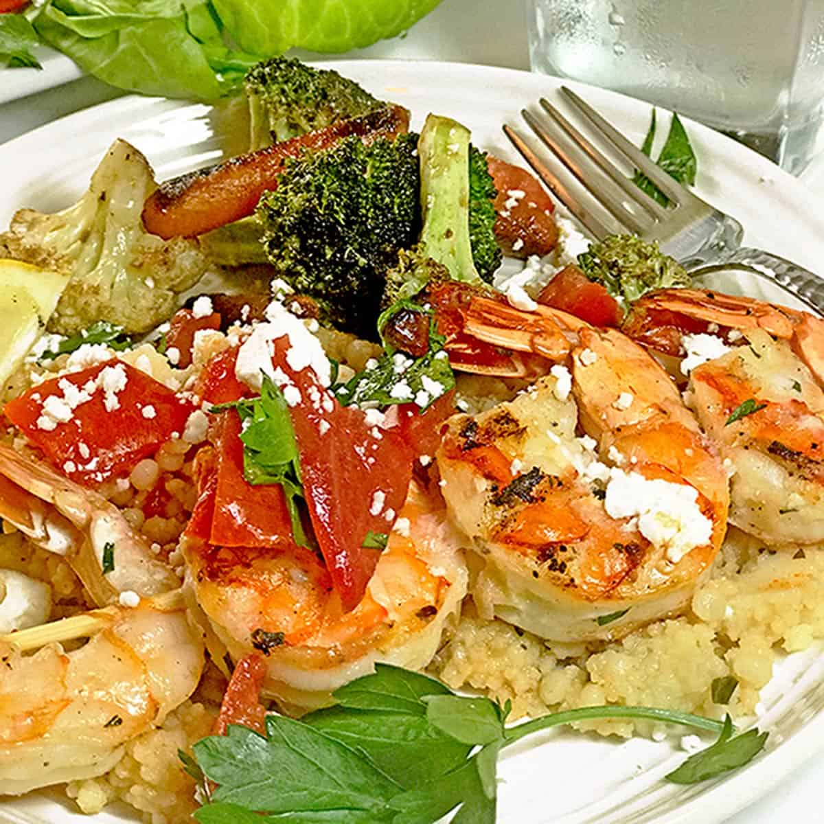 A plate of griled shrimp over couscous.