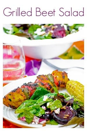 Bowl of salad in back of plated beet salad, corn and kabob on set table