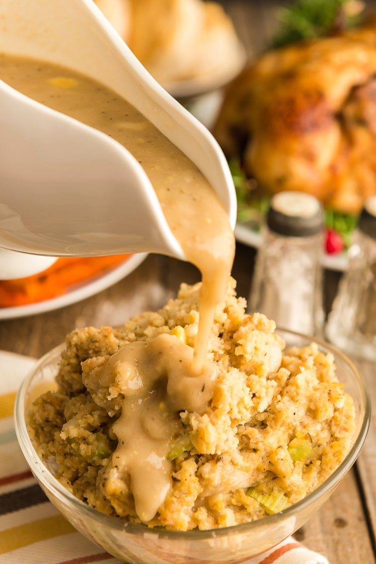 Pouring giblet gravy over homemade cornbread dressing.