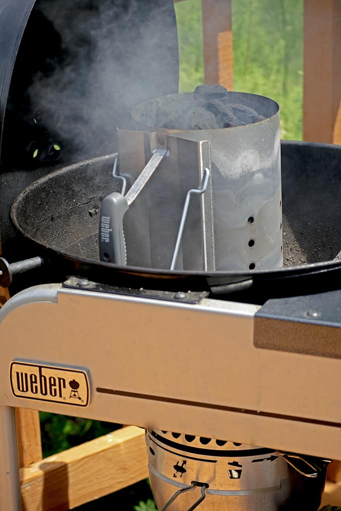A charcoal chimney is a good way to light charcoal when making jerk chicken.
