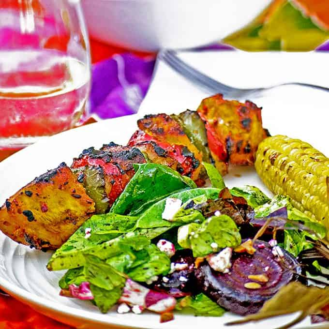 Dinner plate of roasted beet salad, corn, kabob on table with napkin and fork