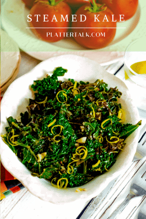 Bowl of steaed kale with lemon zest garnish.