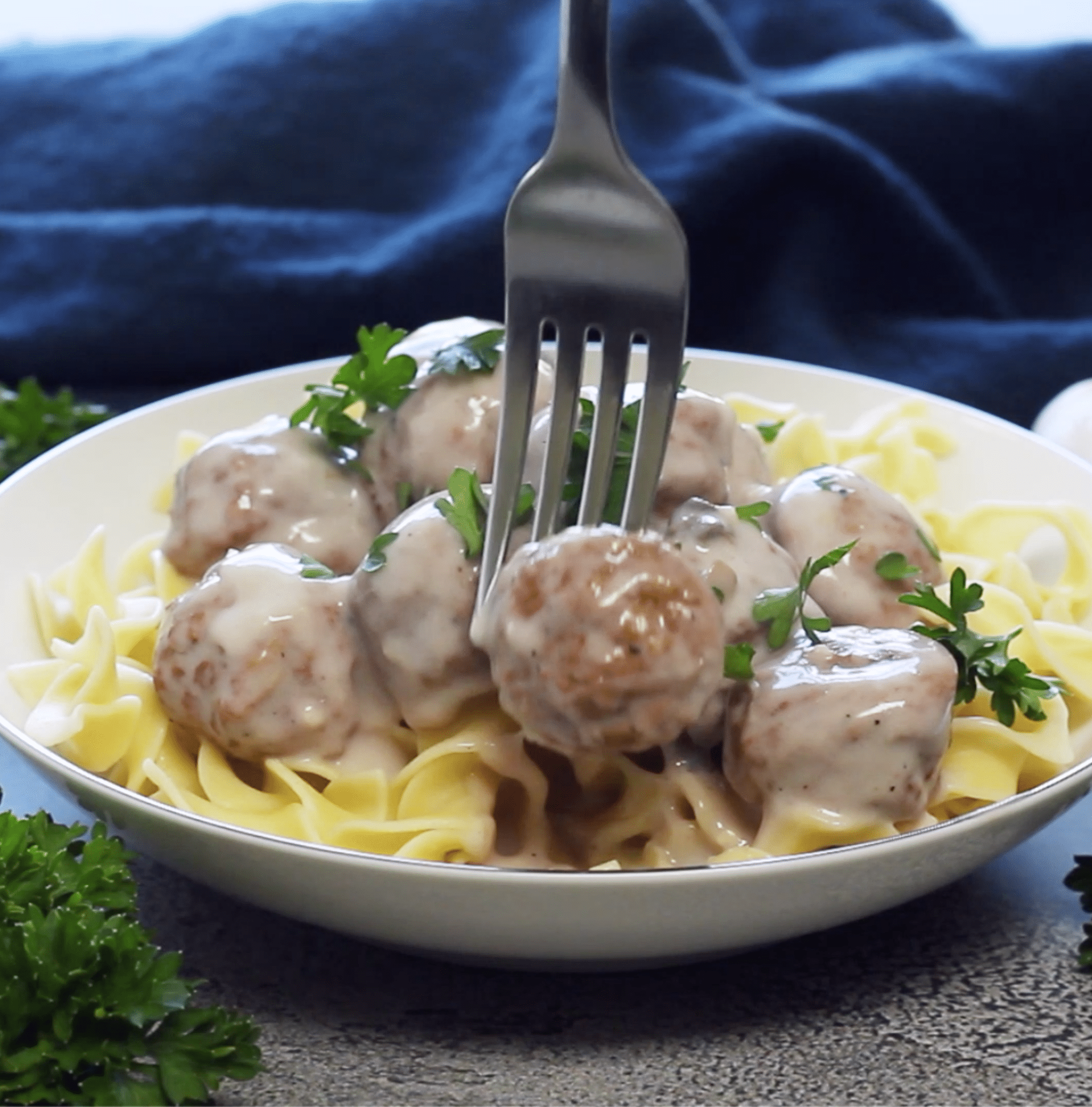 plate of creamy meatballs over egg noodles